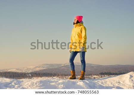 The girl is standing on a snowy hill and looking into the distance. Tourist trip in winter. #748055563