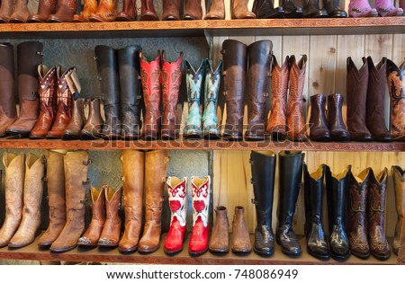 cowboy boots on a shelf in a store, facing straight #748086949