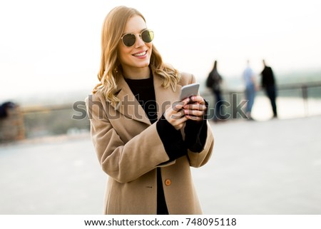 View at modern woman using mobile phone at autumn outdoor #748095118