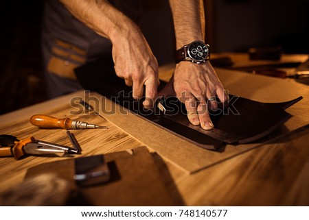 Working process of the leather belt in the leather workshop. Man holding crafting tool and working. Tanner in old tannery. Wooden table background. Royalty-Free Stock Photo #748140577