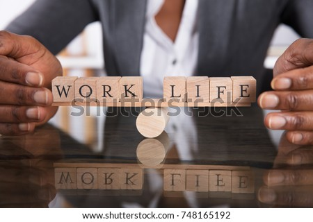Close-up Of A Businesswoman's Hand Covering Balance Between Life And Work On Seesaw Royalty-Free Stock Photo #748165192