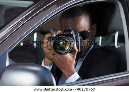 Young African Photographer With Camera Sitting Inside Car #748170769