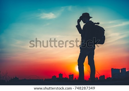 Travel Concept. Silhouette of a man with a backpack against bright sky sunset. Sun goes down. A man looks ahead, straightens his cowboy hat. Cityscape night view in the background. Color toning filter #748287349