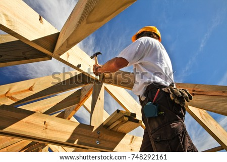 Roofer, carpenter working on roof structure on construction site #748292161