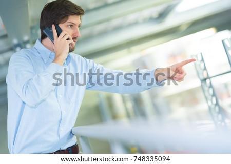 man on cellular phone pointing at something #748335094