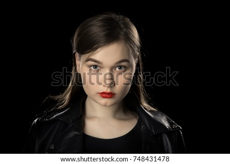 serious young female portrait on black background #748431478