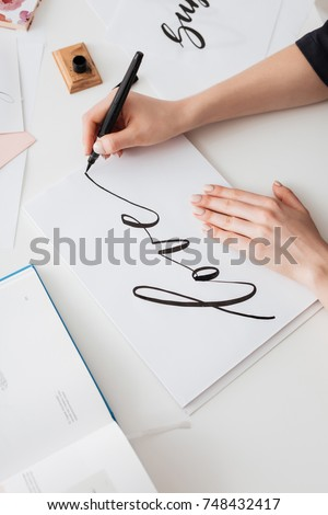 Close up photo of young woman hands writing cute notes on paper on desk isolated