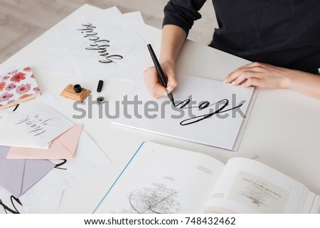 Photo of young woman hands writing beautiful notes on paper with open book on desk isolated