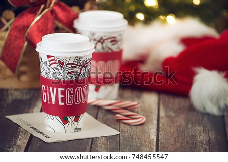 Dallas, TX - November 4, 2017: Starbucks popular holiday beverage, served in the new 2017 designed holiday cups. Displayed with candy canes on wooden rustic table. Christmas hats in the background. #748455547