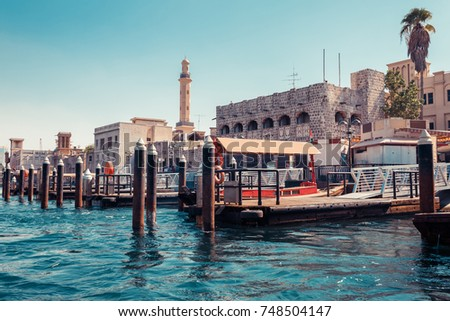 Skyline view of Dubai Creek with traditional boats and piers. Sunny summer day. Famous tourist destination in UAE. #748504147