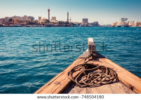 Panoramic view from traditional water taxi boats in Dubai, UAE. Creek gulf and Deira area. United Arab Emirates famous tourist destination. Creative color post processing. #748504180