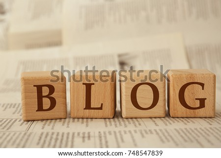 Wooden cubes with word BLOG on paper background #748547839