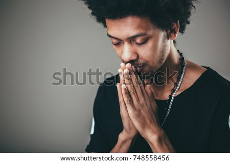 Praying african american man hoping for better. Asking God for good luck, success, forgiveness. Power of religion, belief, worship. Holding hands in prayer, eyes closed. #748558456