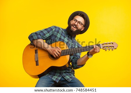 Smiling bearded musician man having fun and playing acoustic guitar.  Royalty-Free Stock Photo #748584451