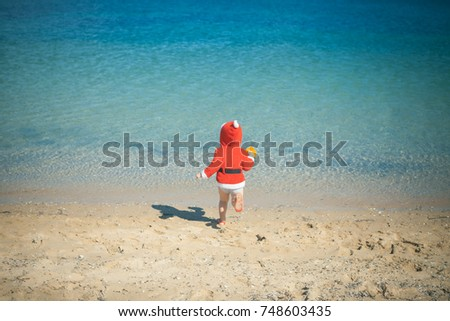 Childhood. Summer. Cute baby boy in red Santa coat with hood and wet shorts walks barefoot in blue sea water on pebble beach on sunny summer day on natural background. Christmas childhood. Santa boy.