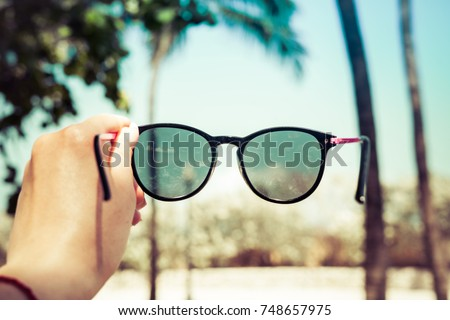 The girl is holding sunglasses in her hand against the background of blurry palms. Travel concept Royalty-Free Stock Photo #748657975