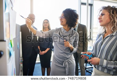 Diverse group of focused businesspeople brainstorming together on a whiteboard during a strategy session in a bright modern office Royalty-Free Stock Photo #748719808