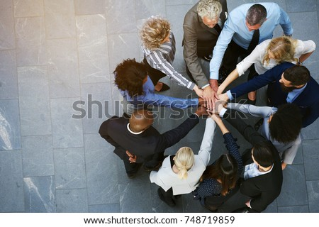 High angle view of a team of united coworkers standing with their hands together in a huddle in the lobby of a modern office building Royalty-Free Stock Photo #748719859