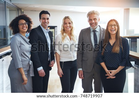 Portrait of a diverse group of confident business colleagues smiling and standing together in the hallway of a modern office #748719907