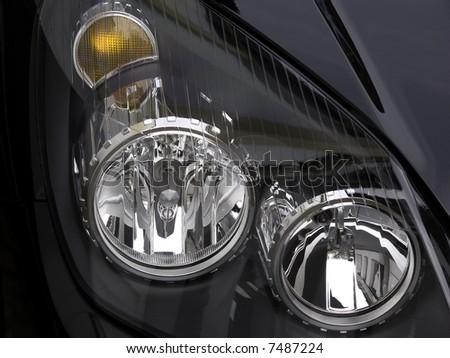 Headlight and blinker of a black car, closeup. #7487224