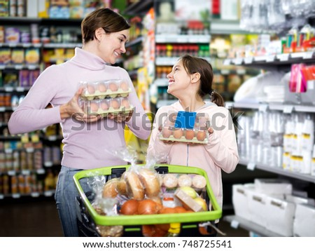Smiling woman customer with girl looking for natural eggs in supermarket #748725541