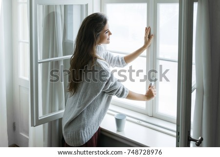 Woman is opening window to look at beautiful snowy landscape outside Royalty-Free Stock Photo #748728976