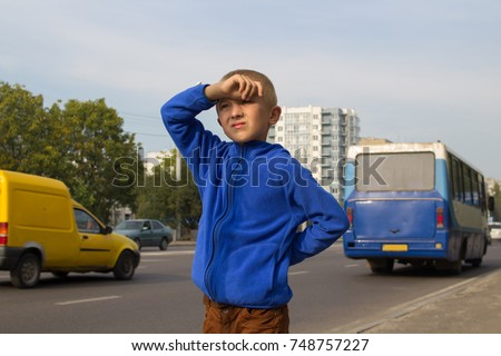 the boy ran out of the house and was waiting for the bus near the road #748757227