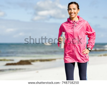 Beautiful girl in sport clothes drinking water after workout on the beach #748758250