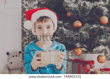 Cute happy boy in santa hat with christmas present box on holiday morning in beautiful room interior. Male child open Xmas gifts near big decorated fir tree and fireplace. Winter holidays concept #748802131