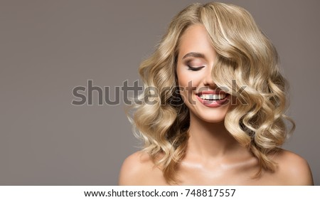 Blonde woman with curly beautiful hair smiling on gray background.  Royalty-Free Stock Photo #748817557