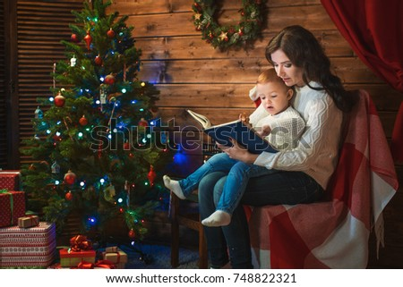 Mother and son celebrate Christmas in a decorated house with a Christmas tree and read the book #748822321