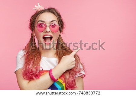 Look there! Surprised astonished lady with pony tails, wears pink sunglasses, has shocked expression, points with fore finger at copy space on pink background. Amazement and wonderment concept