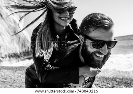 Black&white photo of happy couple in the leather jackets running on the beach Royalty-Free Stock Photo #748840216