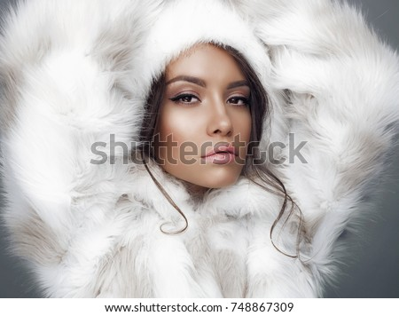 Fashion studio portrait of beautiful lady in white fur coat and fur hat. Winter beauty in luxury. Fashion fur. Beautiful woman in luxury fur coat. Fashion model posing in eco-fur coat and eco-fur hat #748867309