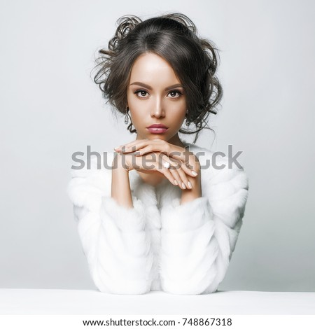 Fashion studio portrait of beautiful lady with elegant hairstyle in white fur coat. Winter beauty in luxury. Fashion fur. Beautiful woman in luxury fur coat. Fashion model posing in eco-fur coat #748867318