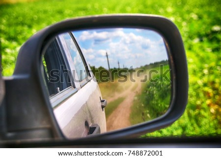 View in the side mirror when driving a crossover at a high speed on a picturesque dusty field road in the summer #748872001