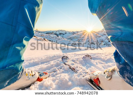 Skier standing in front of wonderful sunset in ski slope - Winter extreme sport concept with athlete on top of the mountain ready to ride down - Focus on intersection skis - Unfiltered photo #748942078