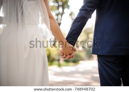 Back view of bride in white dress and groom in suit holding each others hands outdoors #748948702