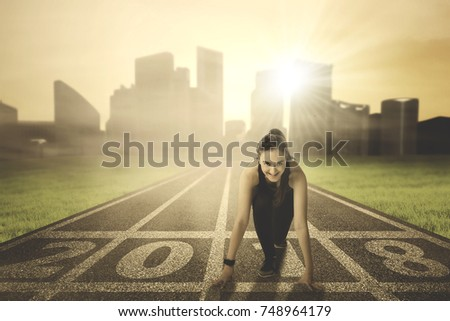 Picture of a beautiful Arabian woman wearing sportswear while kneeling on the track with numbers 2018. Shot at sunrise time