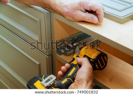 Adjusting fixing cabinet door hinge adjustment on kitchen cabinets Royalty-Free Stock Photo #749001832