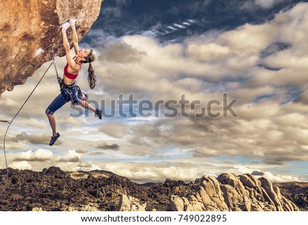 Female climber struggling up a sheer cliff. #749022895