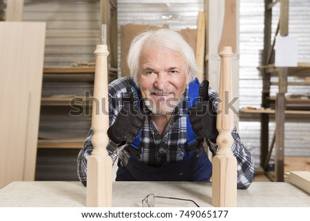 Serious furniture designer carefully polishes the chair frame, which he is busy manufacturing in his woodwork workshop, with shelves of wooden objects and patterns behind him #749065177