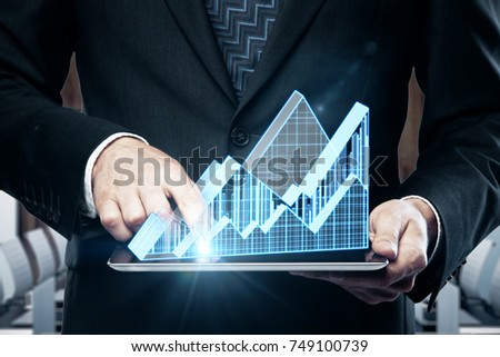 Close up of businessman hands using tablet with abstract glowing business chart hologram on interior background. Economy and sales concept #749100739