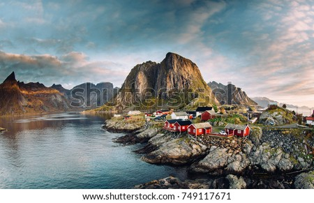 Norwegian fishing village at the Lofoten Islands in Norway. Dramatic sunset clouds moving over steep mountain peaks #749117671