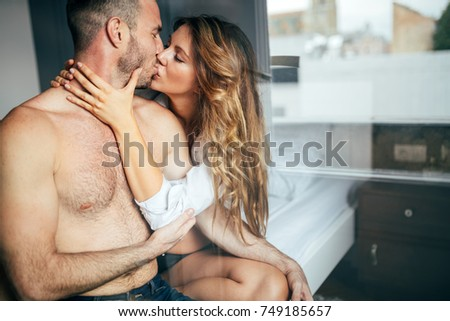 Attractive couple sharing intimate moments in bedroom #749185657