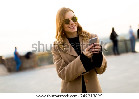 View at modern woman using mobile phone at autumn outdoor #749213695