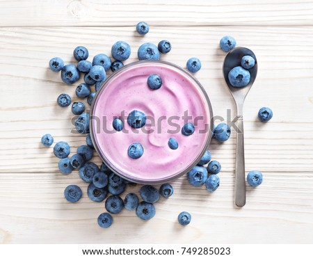 Blueberry yogurt on white wooden table. Fresh yogurt. Healthy food concept. High resolution product. Top view #749285023