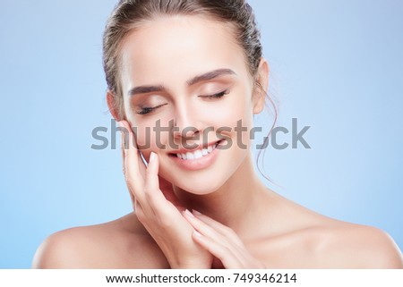 Beauty portrait of woman with closed eyes touching face with slight smile. Head and shoulders of tender woman with nude make-up, beauty concept. Indoors, studio #749346214