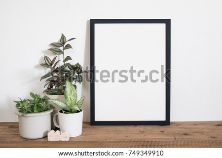 Frame poster with tropical leaf plant in pot on table.lifestyle home decor