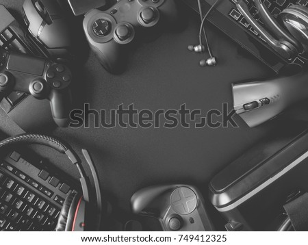 top view of gamer concept with gaming gear, mouse, keyboard, joysticks, headset, VR Headset on black table background with copy space.